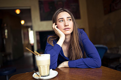 Young woman sitting at table in a cafe looking sideways - p300m2104472 by Philipp Nemenz
