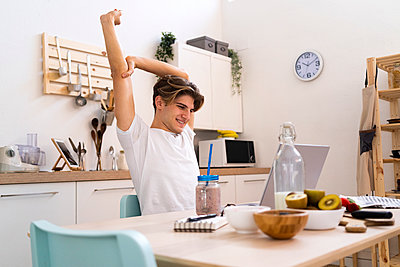 Young man stretching his hand while sitting at table with laptop in kitchen - p300m2266215 by Giorgio Fochesato