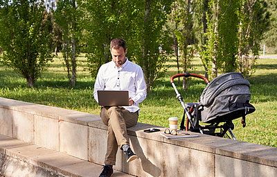 Mid adult businessman working on laptop while sitting by baby stroller in park - p300m2282549 by Veam