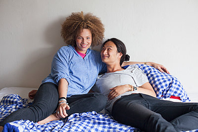 Smiling young couple resting on bed against white wall at home - p301m1535044 by Larry Washburn