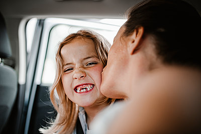 Happy daughter kissed by mother looking at camera - p312m2207714 by Anna Johnsson
