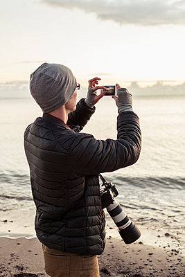 Hiker photographing through smart phone at beach - p426m1407030 by Kentaroo Tryman
