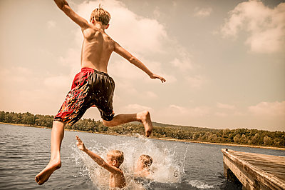 Caucasian boys jumping off wooden dock - p555m1454162 by Jon Feingersh
