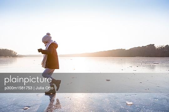 Germany, Brandenburg, Lake Straussee, girl walking on frozen lake - p300m1581753 von Julia Otto
