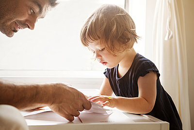 Close-up of father teaching daughter coloring at table in home - p1166m1099402f by Cavan Images