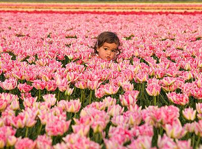 Girl hiding among the tulips - p1231m1043146 by Iris Loonen