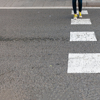 Close-up of woman wearing sneakers crossing street - p300m1580830 by Valentina Barreto