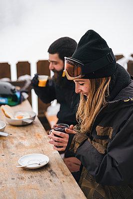 Couple in skiwear having a hot drink at mountain lodge - p300m2029383 von Juri Pozzi