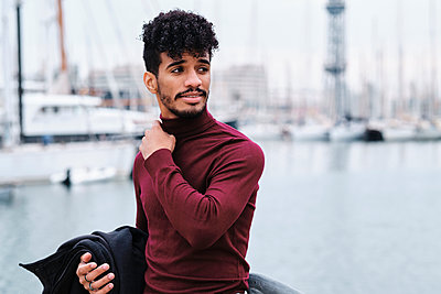 Smiling young man looking away while standing at harbor - p300m2250184 by Alvaro Gonzalez