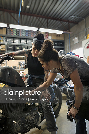 Female motorcycle mechanics talking, fixing motorcycle in auto repair shop