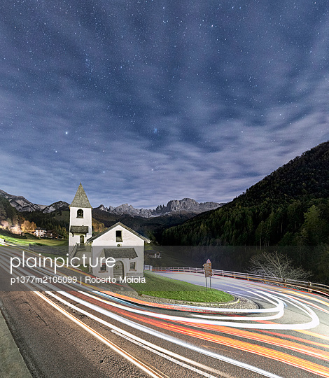 Italy, Trentino-Alto Adige, Bolzano district, Alps, Dolomites, Valle di Tires, Panoramic of lights of car trails, Church of San Cipriano - p1377m2105099 by Roberto Moiola