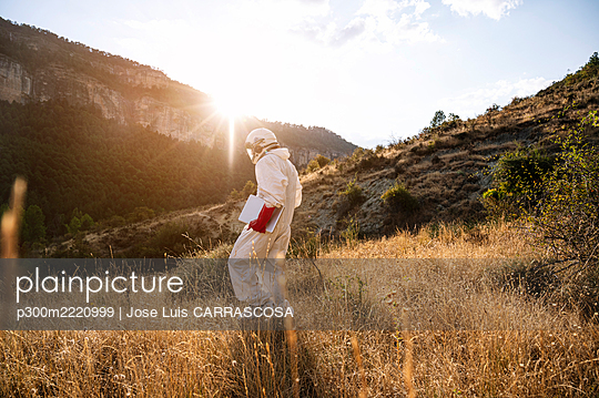 Male astronaut with laptop walking on grassy land against sky during sunny day - p300m2220999 by Jose Luis CARRASCOSA