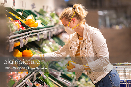 Teenage girl wearing protectice mask and gloves choosing bell peppers at supermarket - p300m2225048 by Anke Scheibe