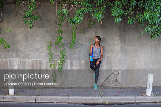 Young female runner listening to earphones leaning against  city sidewalk wall - p924m2090590 by Bean Creative