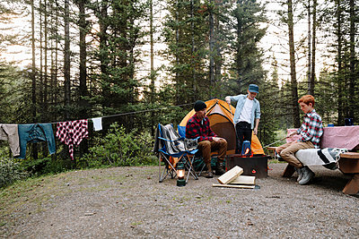 Father and sons relaxing around campsite campfire - p1192m2129287 by Hero Images