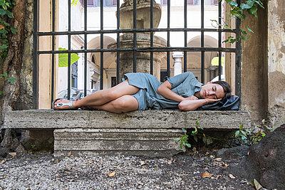 Junge Frau schläft auf einer Steinbank - p1437m2008228 von Achim Bunz