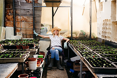 Young woman gardening in a greenhouse - p300m2103554 von Epiximages