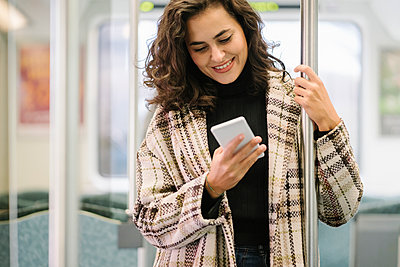 Smiling young woman using smartphone on a subway - p300m2143443 von Hernandez and Sorokina