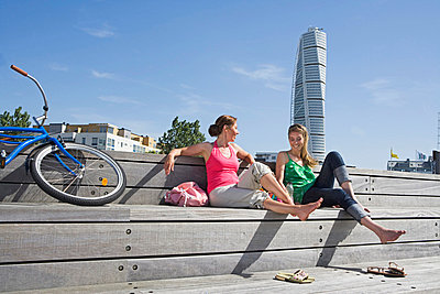 Two friends enjoying the sun Malmo Skane Sweden. - p31221107f by Plattform