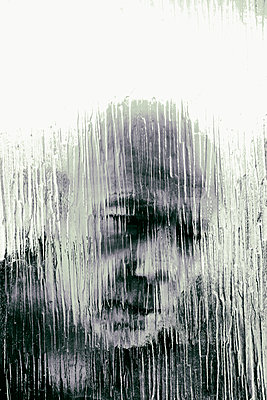 Mans face through textured glass window - p597m2182575 by Tim Robinson