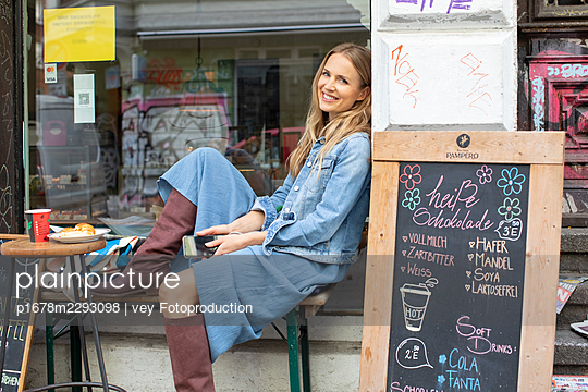 Woman sitting at a bistro - p1678m2293098 by vey Fotoproduction