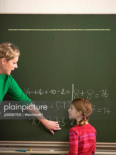 Teacher explaining arithmetic problem to girl (4-7)