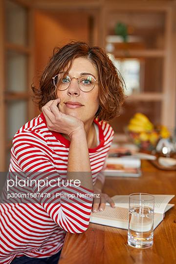 Portrait of mature woman with book at home - p300m1587478 von Philipp Nemenz