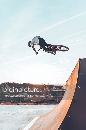 Carefree man performing stunt with bicycle on ramp against sky in park at sunset - p300m2206498 by Aitor Carrera Porté