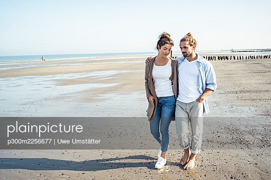 Young couple with hands in pockets taking walk on beach during sunny day - p300m2256677 by Uwe Umstätter