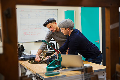 Two men, tailors leaning over a workbench discussing a project, planning their work. - p1100m1522459 by Mint Images