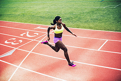 High angle view of determined female athlete running on tracks - p1166m1086173f by John Trice
