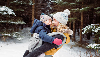 Happy mother carrying daughter in forest during winter - p1166m1554524 by Cavan Images