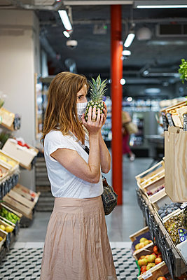 A woman wearing a cloth mask is smelling a pineapple  - p1610m2208826 by myriam tirler