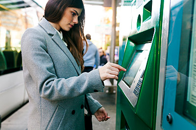 Spain, Barcelona, woman buying ticket from automated machine at  station - p300m1587899 von Valentina Barreto
