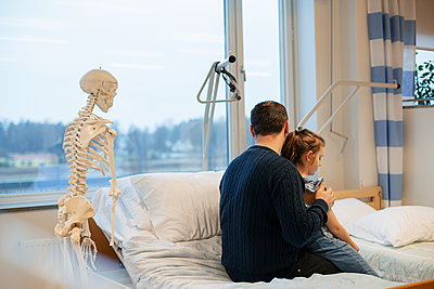 Father with daughter in examination room - p312m2174391 by Scandinav