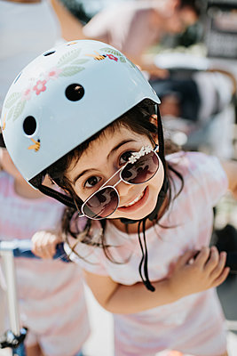 Toddler with safety helmet peering over sunglasses  - p924m2153104 by Sara Monika