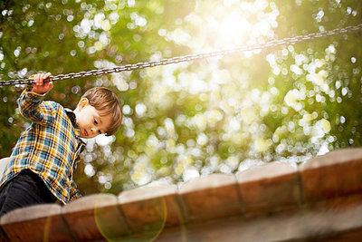 Male toddler crossing wooden footbridge - p924m807093f by Sydney Bourne