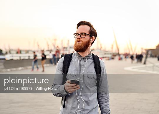 Mann mit Smartphone auf dem Arbeitsweg - p1124m1169979 von Willing-Holtz