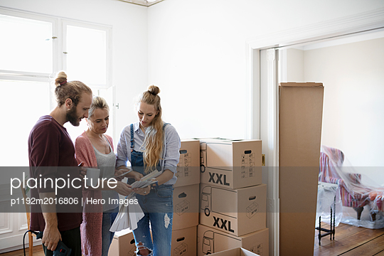 Multi-generation family looking at paint swatches, moving into new home - p1192m2016806 by Hero Images