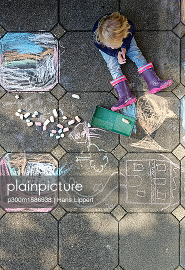 Little girl after drawing with chalk outdoors, top view - p300m1586938 von Hans Lippert
