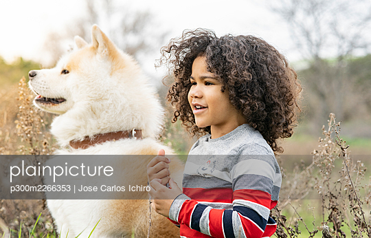 Boy looking away by dog in nature - p300m2266353 by Jose Carlos Ichiro