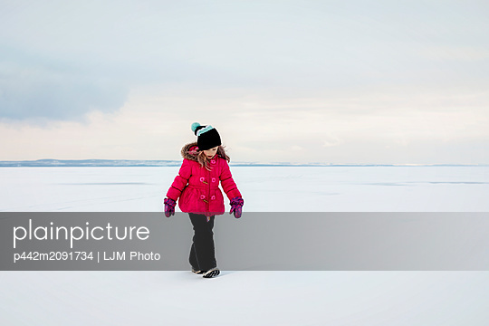 A young girl walking on a frozen lake while ice fishing during a winter family outing on Lake Wabamun: Wabamun, Alberta, Canada - p442m2091734 by LJM Photo