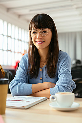 Portrait of smiling young woman with tepad at desk in office - p300m1587100 by Bonninstudio