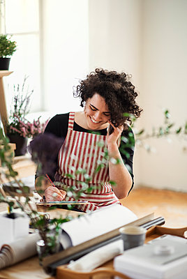 Happy young woman on the phone in a small shop with plants - p300m2144001 von HalfPoint
