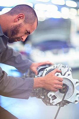 Car mechanic working on gearbox in repair garage - p300m975568f by zerocreatives