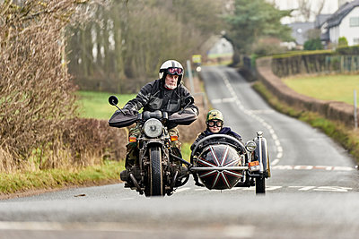 Senior man and grandson riding motorcycle and sidecar on rural road - p429m1226739 by GS Visuals