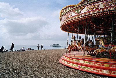 Brighton, Karussell an steinigem Strand im Sommer mit Ruine eines einstigen Piers im Hintergrund - p627m1035567 von Kristin Hoell