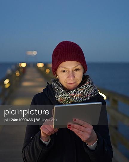 Frau mit Ipad auf Seebrücke - p1124m1090466 von Willing-Holtz