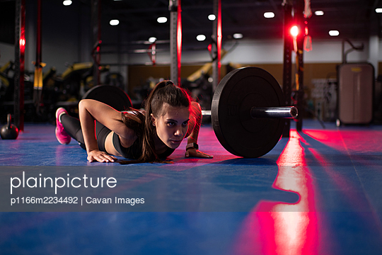 Powerful woman lying doing exercise on floor - p1166m2234492 by Cavan Images