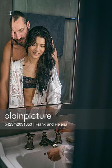 Semi-naked hipster couple washing hands in bathroom - p429m2091353 by Frank and Helena